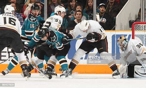 Scott Nichol of the San Jose Sharks searches for the puck between the legs of Brett Festerling and Petteri Nokelainen of the Anaheim Ducks while...