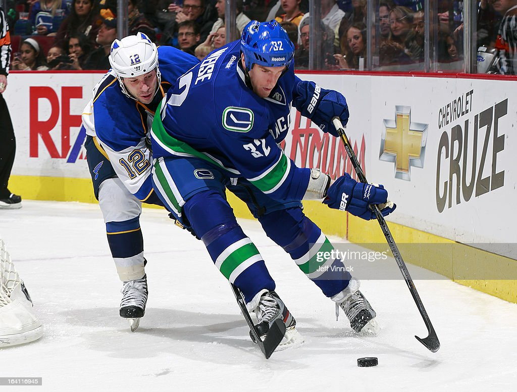 Scott Nichol #12 of the St. Louis Blues checks Dale Weise #32 of the Vancouver Canucks skates up ice with the puck during their NHL game at Rogers Arena March 19, 2013 in Vancouver, British Columbia, Canada. Vancouver won 3-2.