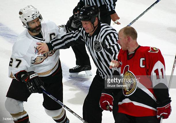 Scott Niedermayer of the Anaheim Ducks and Daniel Alfredsson of the Ottawa Senators are seperated by the linesman after the end of the second period...