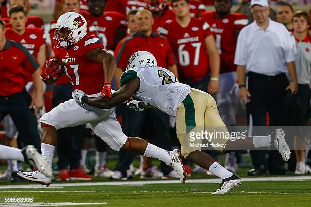 J Scott of the Louisville Cardinals runs the ball as Alan Barnwell of the Charlotte 49ers attempts the tackle at Papa John's Cardinal Stadium on...