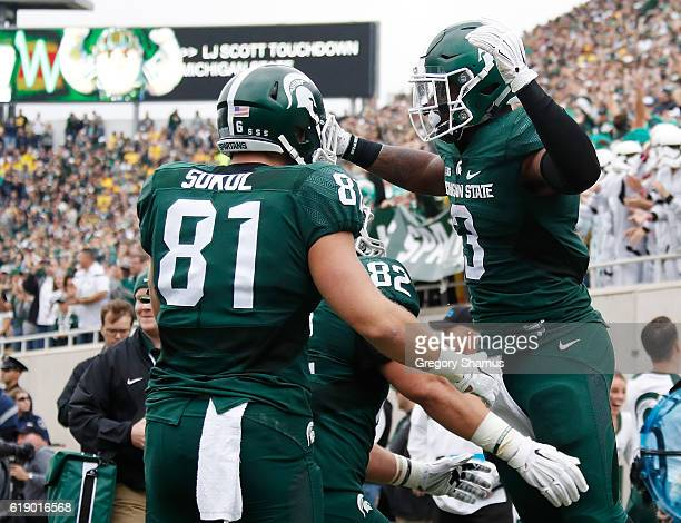 Scott of the Michigan State Spartans celebrates a first quarter touchdown with Matt Sokol while playing the Michigan Wolverines at Spartan Stadium on...