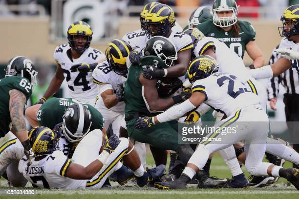 Scott of the Michigan State Spartans is tackled by the Michigan Wolverines defense during a second half run at Spartan Stadium on October 20 2018 in...