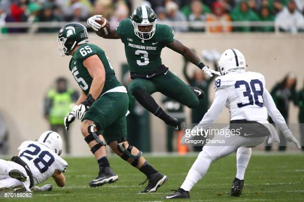 Scott of the Michigan State Spartans jumps past the tackle of Troy Apke of the Penn State Nittany Lions during the first half at Spartan Stadium on...
