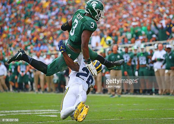 Scott of the Michigan State Spartans runs for a short gain as Jourdan Lewis of the Michigan Wolverines makes the stop during the fourth quarter of...