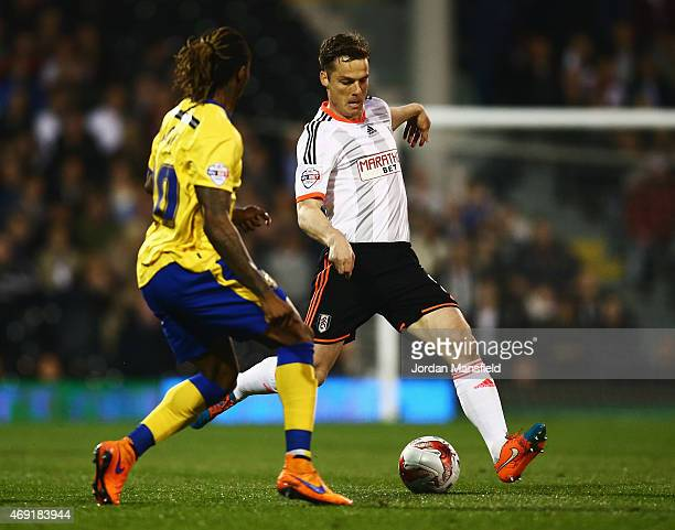 Scott Parker of Fulham is watched by Gaetan Bong of Wigan Athletic during the Sky Bet Championship match between Fulham and Wigan Athletic at Craven...