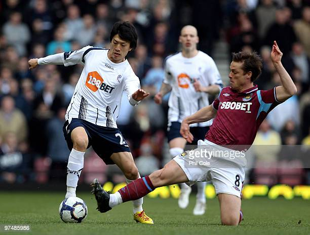 Scott Parker of West Ham United tackles Lee ChungYong of Bolton Wanderers during the Barclays Premier League match between West Ham United and Bolton...