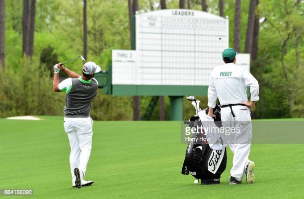 Scott Piercy of the United States hits a shot on the second hole as his caddie looks on during a practice round prior to the start of the 2017...