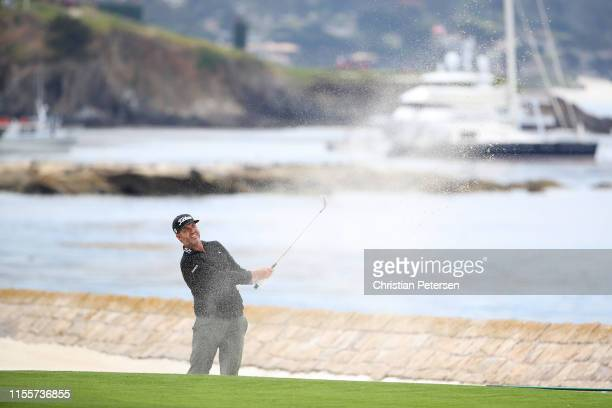 Scott Piercy of the United States plays a shot from a bunker on the 18th hole during the first round of the 2019 US Open at Pebble Beach Golf Links...