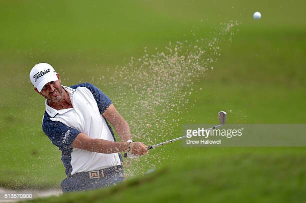 Scott Piercy takes his second shot out of the bunker on the 10th hole during the first round of the World Golf ChampionshipsCadillac Championship at...