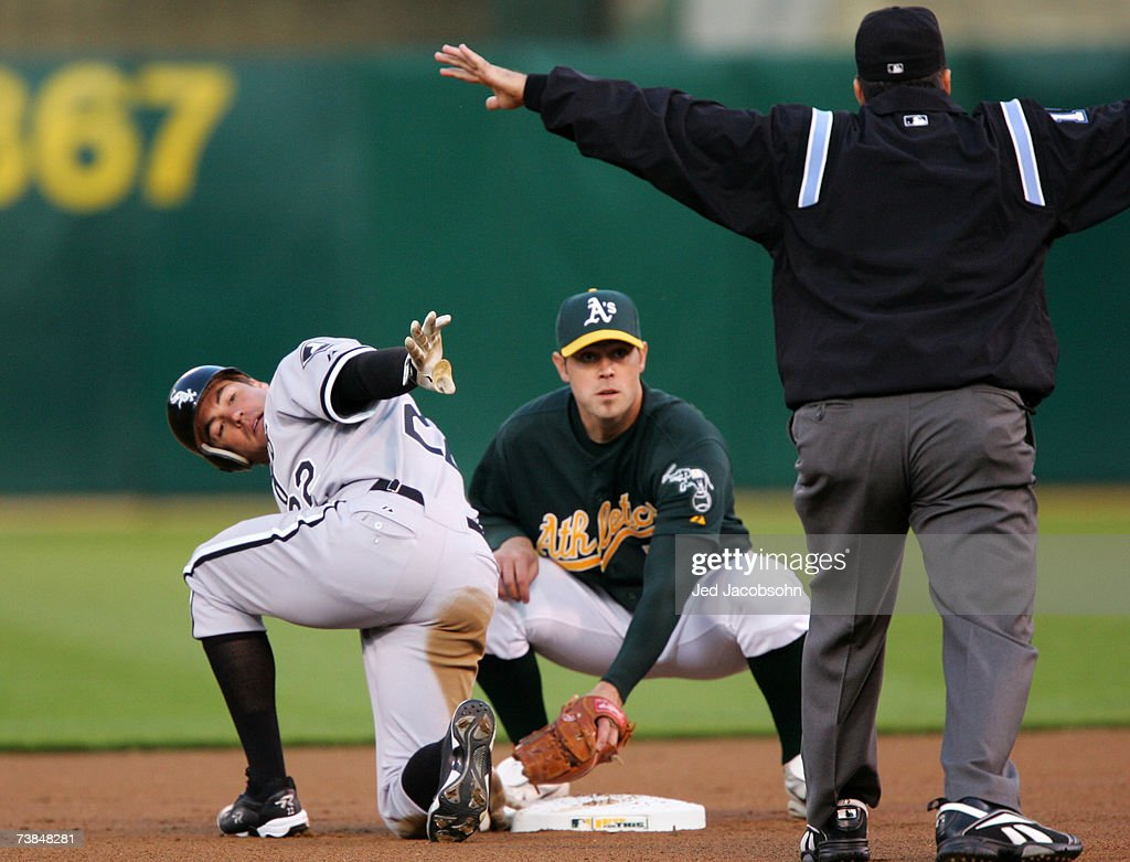 Scott Podsednik #22 of the Chicago White Sox slides into second base with a double as Bobby Crosby #7 of the Oakland Athletics looks on at McAfee Coliseum April 9, 2007 in Oakland, California.