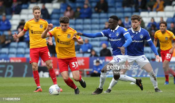 Scott Pollock of Northampton Town looks to move forward with the ball away from Chinedu Uche of Oldham Athletic during the Sky Bet League Two match...