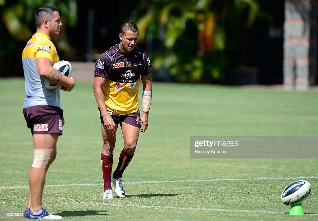 Scott Prince lines up a kick for goal as team mate Corey Parker watches on during a Brisbane Broncos NRL training session on March 7, 2013 in Brisbane, Australia.