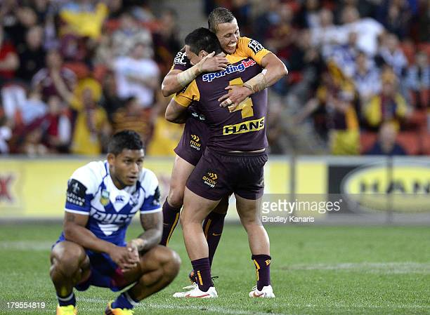 Scott Prince of the Broncos celebrates victory after his 300th and final match as Ben Barba of the Bulldogs is dejected after the round 26 NRL match...
