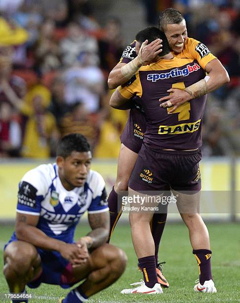 Scott Prince of the Broncos celebrates victory in his final match in the NRL as Ben Barba is dejected after the round 26 NRL match between the...