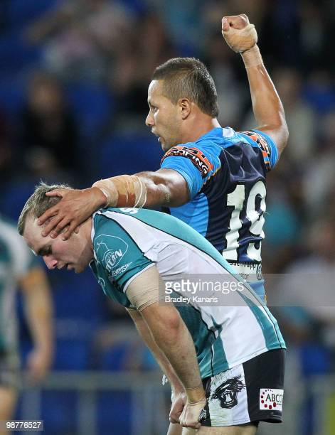 Scott Prince of the Titans pats Lule Walsh of the Panthers on the head after assisting in a try to team mate Ashley Harrison during the round eight...