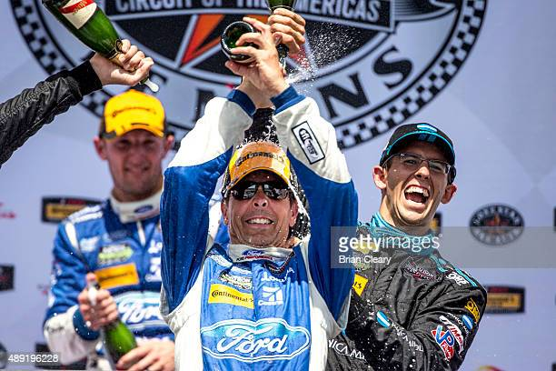 Scott Pruett center is doused with champagne by fellow competitors after winning the IMSA Tudor Series race at Circuit of The Americas on September...
