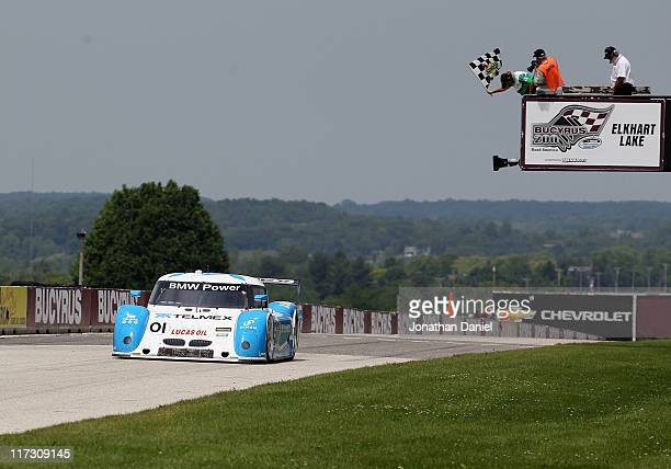 Scott Pruett driver of the 01 Chip Ganassi Racing with Felix Sabates BMW Riley crosses the finish line to win the GrandAm Rolex Series at Road...