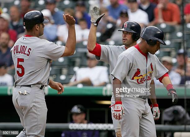 Scott Pujols and Mark Grudzielanek of the St Louis Cardinals celerbate behind teammate Abraham Nunez after they scored on a Scott Seabol first inning...