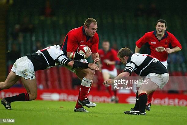 Scott Quinnell of Llanelli is tackled by Matthew Nuthall and Jon Bryant of Pontypridd during the Principality Cup Final played at the Millennium...