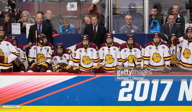 Scott Sandelin Head Coach of the Minnesota Duluth Bulldogs stands behind the bench during a game against the Harvard Crimson during game one of the...
