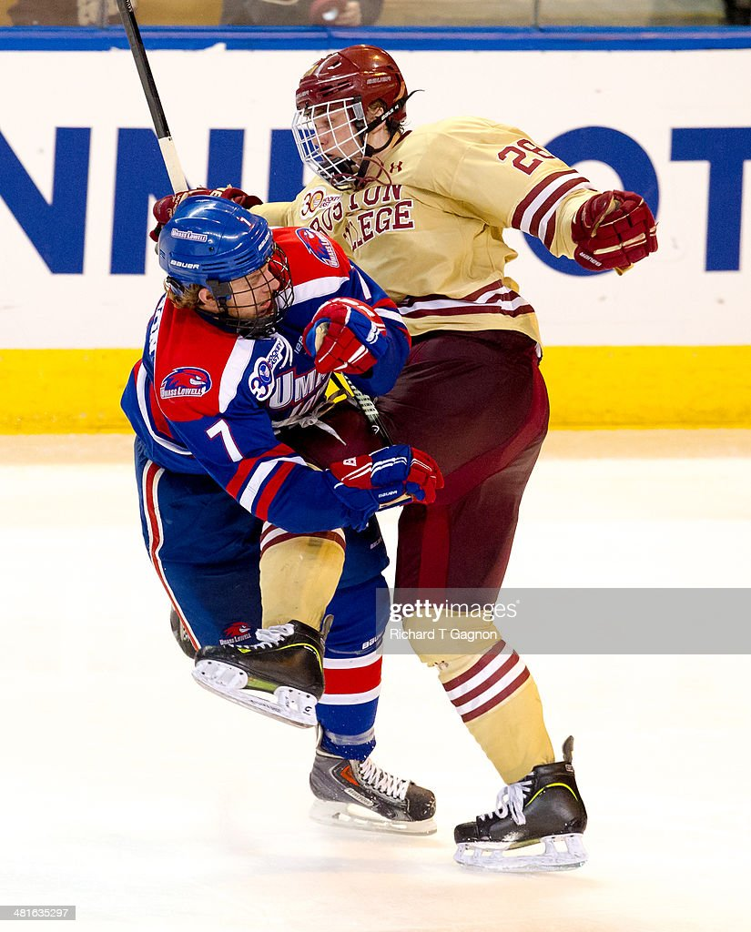 Scott Savage #28 of the Boston College Eagles checks Shayne Thompson #7 of the Massachusetts Lowell River Hawks during the NCAA Division I Men's Ice Hockey Northeast Regional Championship Final at the DCU Center on March 30, 2014 in Worcester, Massachusetts.