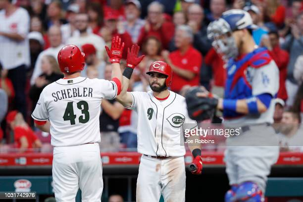 Scott Schebler of the Cincinnati Reds celebrates with Jose Peraza after hitting a solo home run in the third inning of the game against the Los...