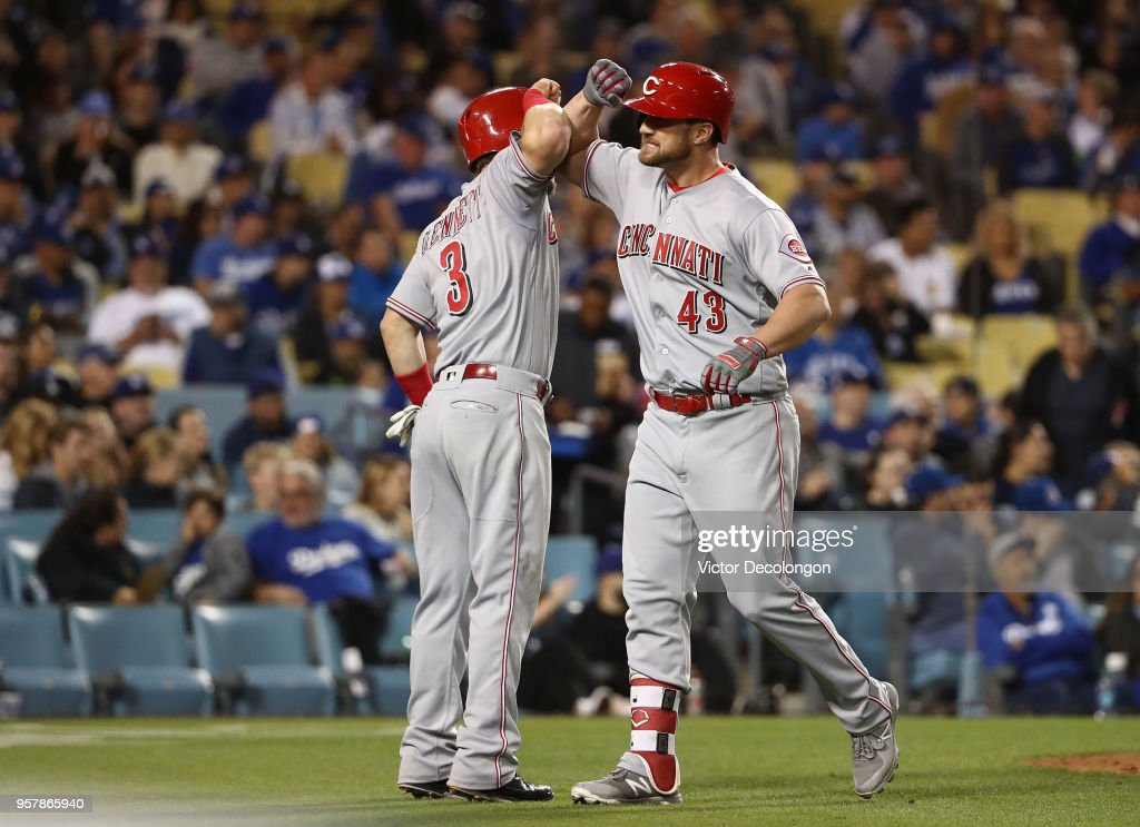 Scott Schebler #43 of the Cincinnati Reds celebrates with teammate Scooter Gennett #3 in the infield after Schebler hit a three-run homerun to left field to take a 4-3 lead in the sixth inning of the MLB game against the Los Angeles Dodgers at Dodger Stadium on May 12, 2018 in Los Angeles, California. The Reds defeated the Dodgers 5-3.
