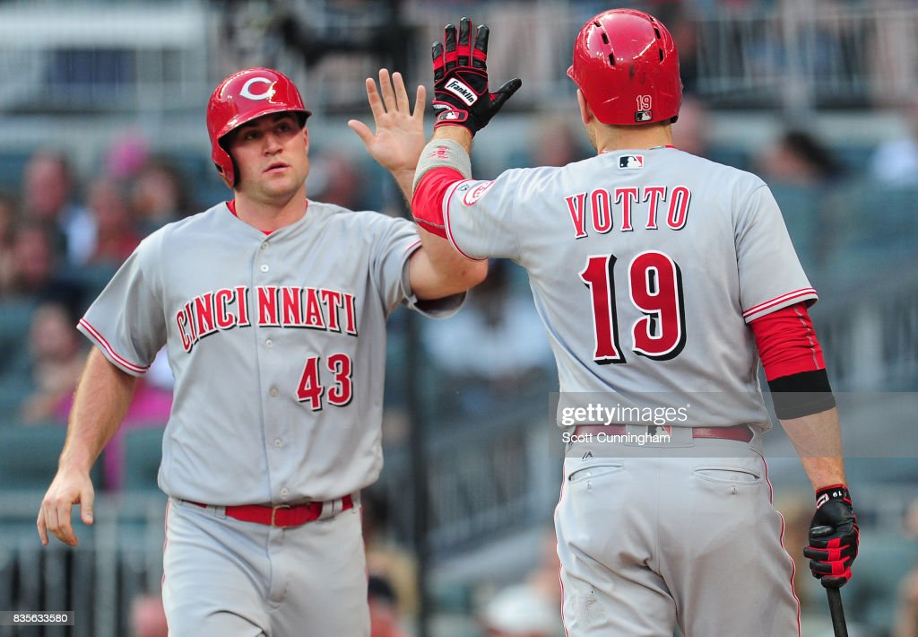 Scott Schebler #43 of the Cincinnati Reds is congratulated by Joey Votto #19 after scoring a third inning run against the Atlanta Braves at SunTrust Park on August 19, 2017 in Atlanta, Georgia.