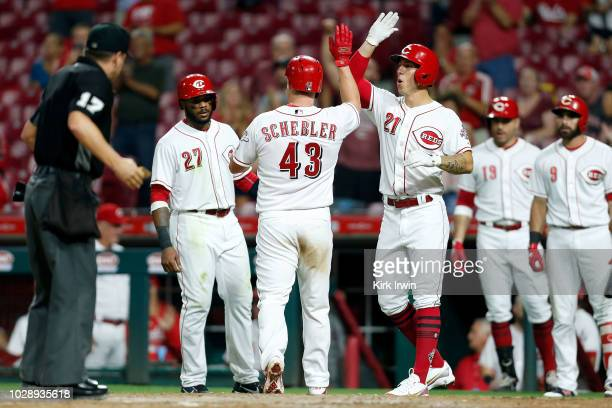 Scott Schebler of the Cincinnati Reds is congratulated by Phillip Ervin and Michael Lorenzen after hitting a grand slam during the sixth inning of...