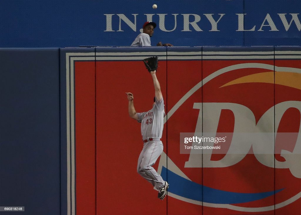 Scott Schebler #43 of the Cincinnati Reds makes a leaping catch against the wall in the fourth inning during MLB game action as Kendrys Morales #8 of the Toronto Blue Jays is denied an extra-base hit at Rogers Centre on May 30, 2017 in Toronto, Canada.