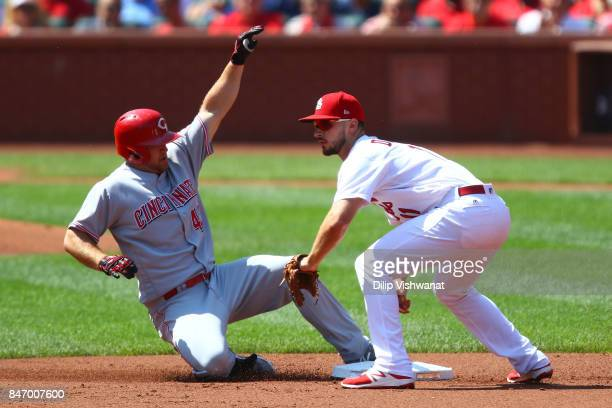 Scott Schebler of the Cincinnati Reds slides safely into second base for a double against Paul DeJong of the St Louis Cardinals in the second inning...