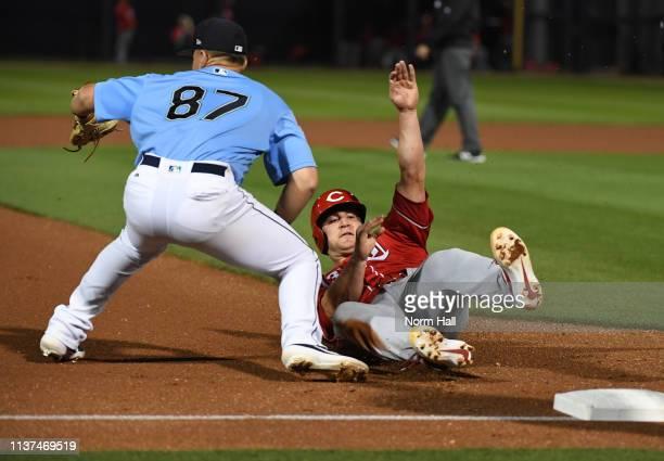 Scott Schebler of the Cincinnati Reds slides safely into third base as Bobby Honeyman of the Seattle Mariners waits for the ball during the fourth...