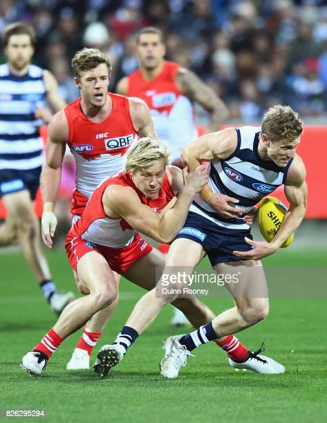 Scott Selwood of the Cats is tackled by Isacc Heeney of the Swans during the round 22 AFL match between the Geelong Cats and the Sydney Swans at...