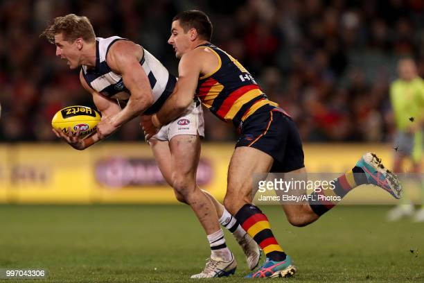 Scott Selwood of the Cats is tackled by Taylor Walker of the Crows during the 2018 AFL round 17 match between the Adelaide Crows and the Geelong Cats...