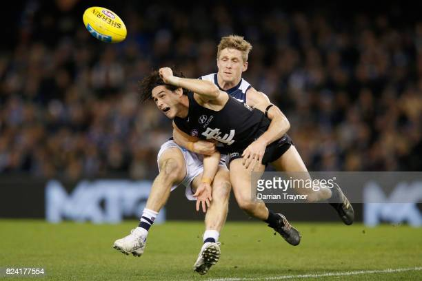 Scott Selwood of the Cats tackles Zac Fisher of the Blues during the round 19 AFL match between the Carlton Blues and the Geelong Cats at Etihad...