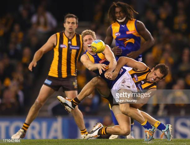 Scott Selwood of the Eagles handballs whilst being tackled by Luke Hodge of the Hawks during the round 13 AFL match between the Hawthorn Hawks and...