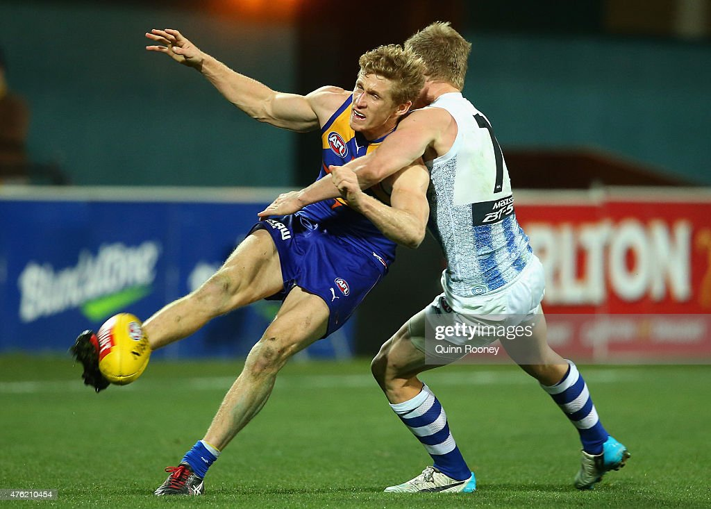 Scott Selwood of the Eagles kicks whilst being tackled by Jack Ziebell of the Kangaroos during the round 10 AFL match between the North Melbourne Kangaroos and the West Coast Eagles at Blundstone Arena on June 7, 2015 in Hobart, Australia.