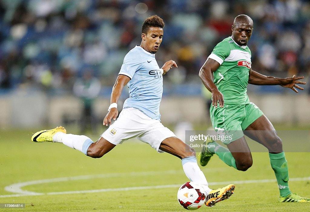 Scott Sinclair of Manchester City shoots past Carlington Nyadombo of Amazulu during the Nelson Mandela Football Invitational match between AmaZulu and Manchester City at Moses Mabhida Stadium on July 18, 2013 in Durban, South Africa.