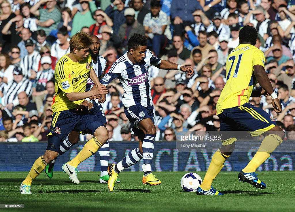 Scott Sinclair of West Bromwich Albion tackled by Ki Sung Yeung of Sunderland during the Barclays Premier League match between West Bromwich Albion and Sunderland at The Hawthorns on September 21, 2013 in West Bromwich, England.