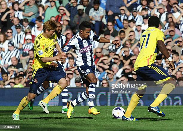 Scott Sinclair of West Bromwich Albion tackled by Ki Sung Yeung of Sunderland during the Barclays Premier League match between West Bromwich Albion...