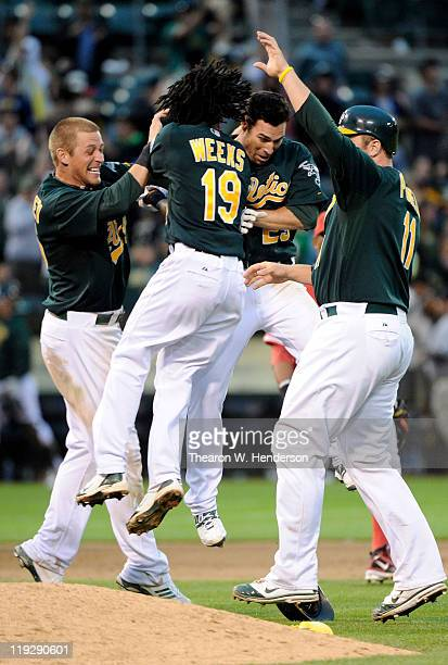Scott Sizemore, Jemile Weeks, Ryan Sweeney and Landon Powell of the Oakland Athletics celebrates after Sizemore hit a walk off RBI double against the...