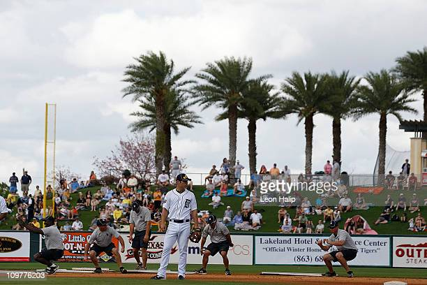 Scott Sizemore of the Detroit Tigers warms up as the Tigers ground crew dance between innings during the game against the Baltimore Orioles at Joker...