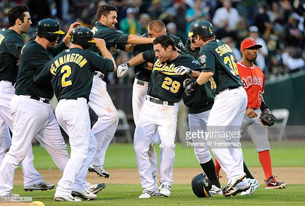 Scott Sizemore of the Oakland Athletics celebrates with teammates after he hit a walk off RBI double against the Los Angeles Angels of Anaheim in the...