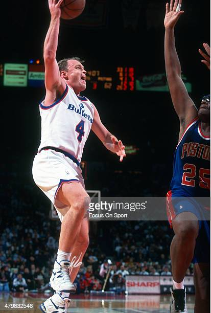 Scott Skiles of the Washington Bullets shoots over Oliver Miller of the Detroit Pistons during an NBA basketball game circa 1994 at the Capital...