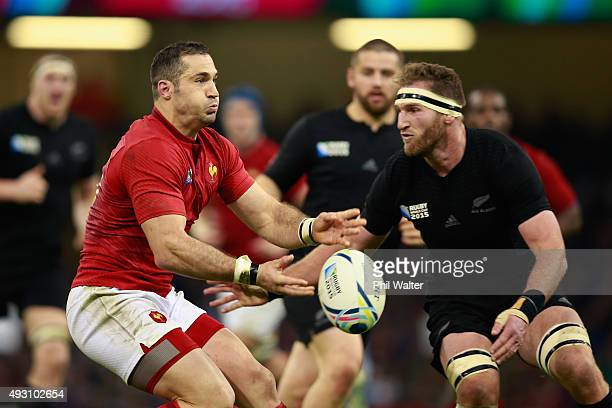 Scott Spedding of France passes under pressure from Kieran Read of the New Zealand All Blacks during the 2015 Rugby World Cup Quarter Final match...