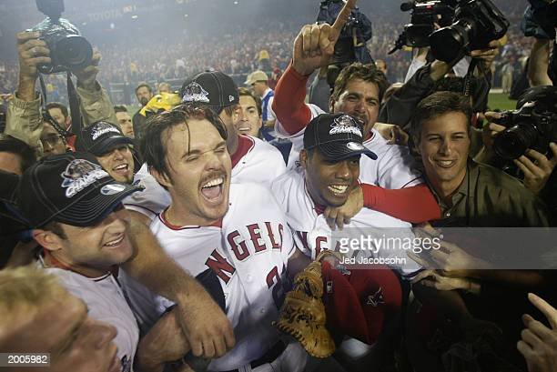 Scott Spiezio of the Anaheim Angels rejoices with teammates Adam Kennedy Alex Ochoa and others after the victory over the San Francisco Giants in...