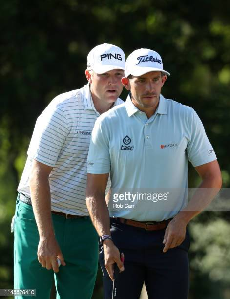 Scott Stallings and Trey Mullinax of the United States prepare to putt on the 15th green during the third round of the Zurich Classic at TPC...