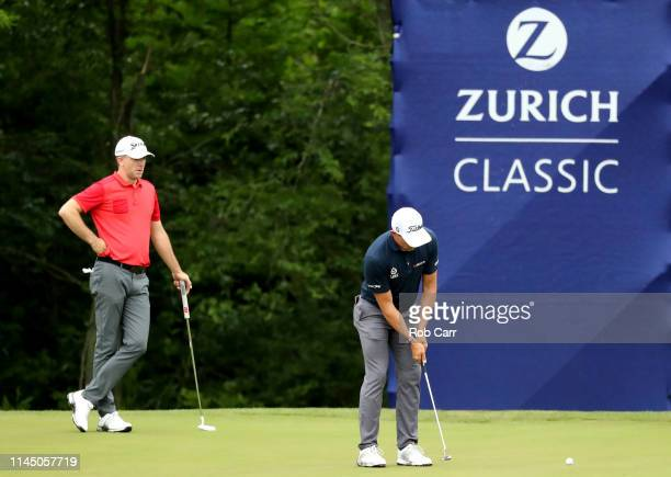 Scott Stallings of the United States putts as Martin Laird of Scotland looks on at the 15th green during the first round of the Zurich Classic at TPC...