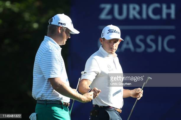 Scott Stallings reacts with Trey Mullinax of the United States on the 15th hole during the continuation of the second round of the Zurich Classic at...