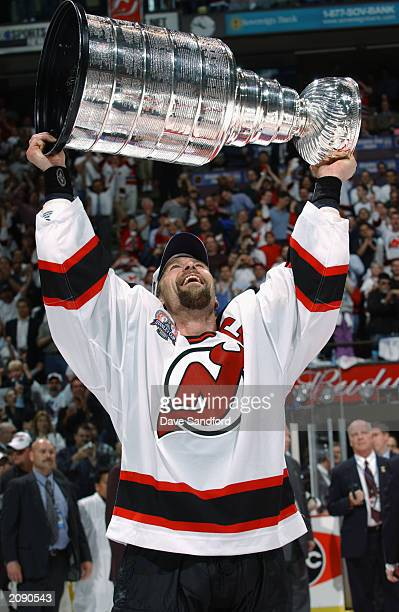 Scott Stevens of the New Jersey Devils holds up the Stanley Cup after beating the Mighty Ducks of Anaheim in game seven of the 2003 Stanley Cup...
